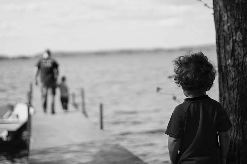 ledsen unge tittar på en man som håller handen på sitt barn