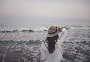 kvinna som håller sin hatt