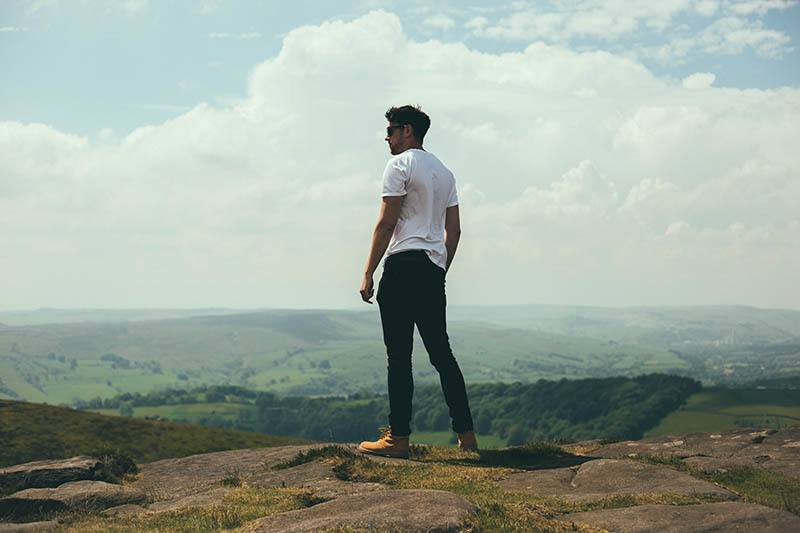 man i vit skjorta som står på kullen