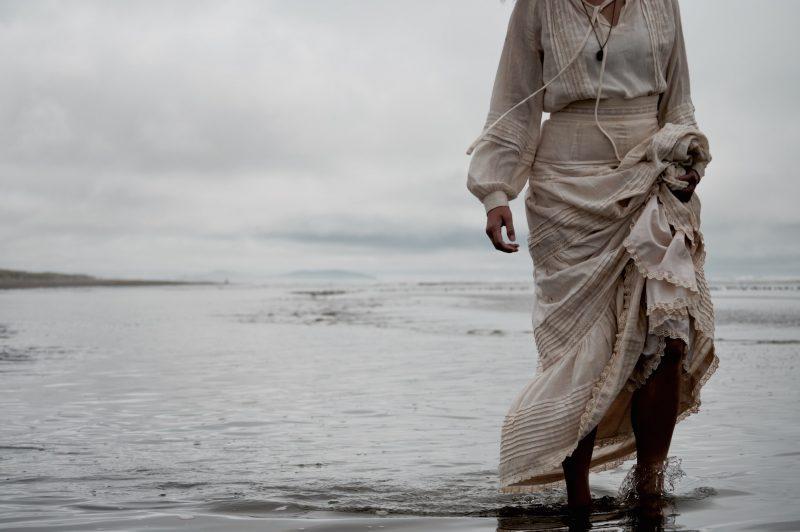 kvinna i lång vit klänning på stranden