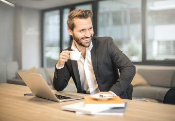 man dricker cofe på kontoret och ler