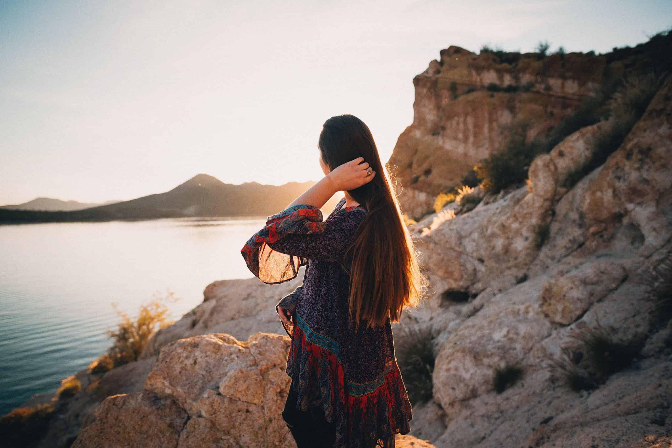 kvinna håller hår och tittar på sjön