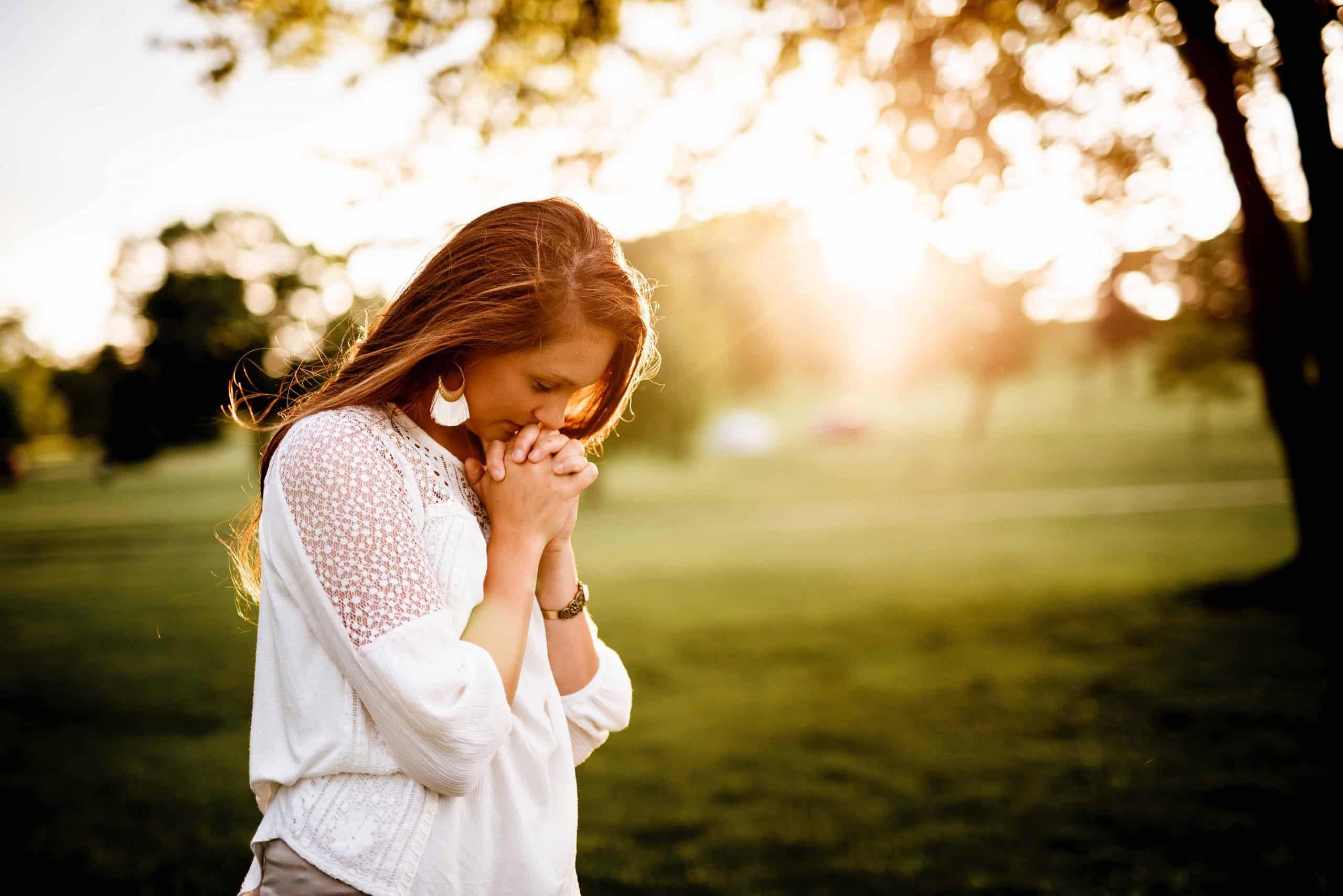 kvinna korsar fingrarna och tittar mot marken