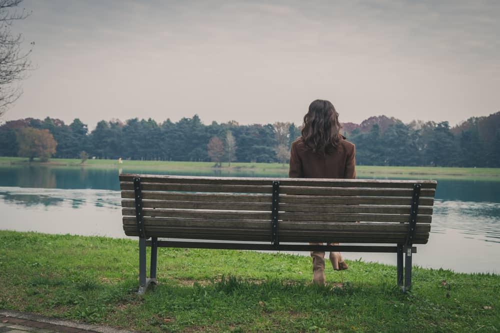 ensam kvinna som sitter i parken