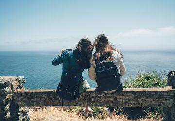 två kvinnliga vänner som sitter framför havet