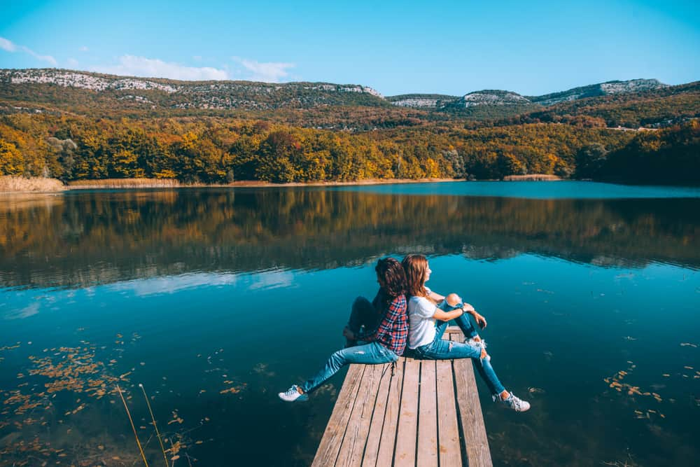 Två vänner som sitter vid sjön