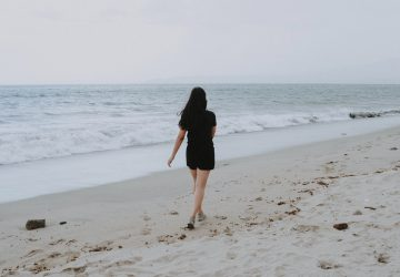 kvinna som går på stranden