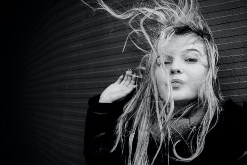 blond kvinna med rörigt hår i vinden