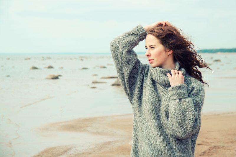 kvinna som bär en varm kofta på stranden.