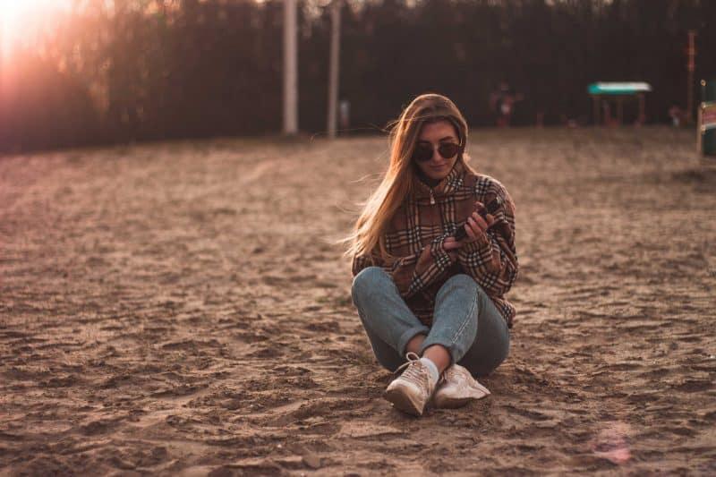 kvinna som håller en telefon som står ensam på stranden