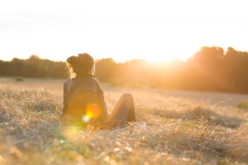 kvinna som sitter på gräset och tittar på solnedgången