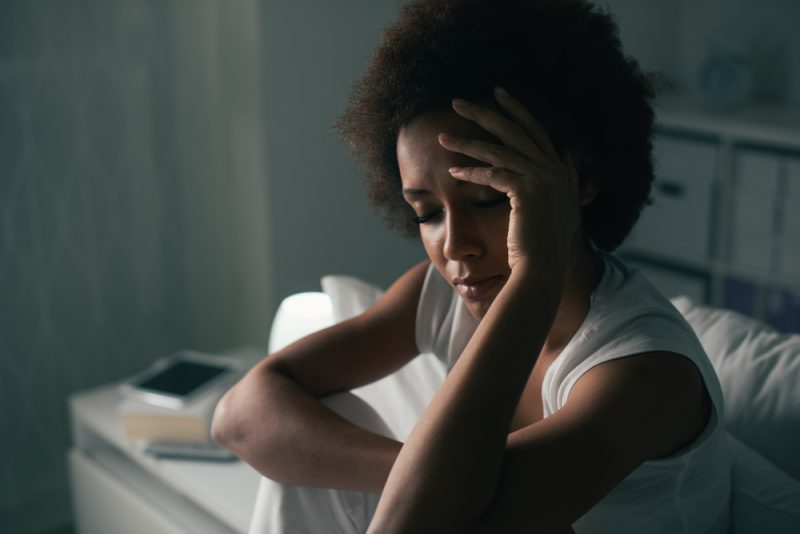 ledsen vacker kvinna med lockigt hår som sitter på sängen