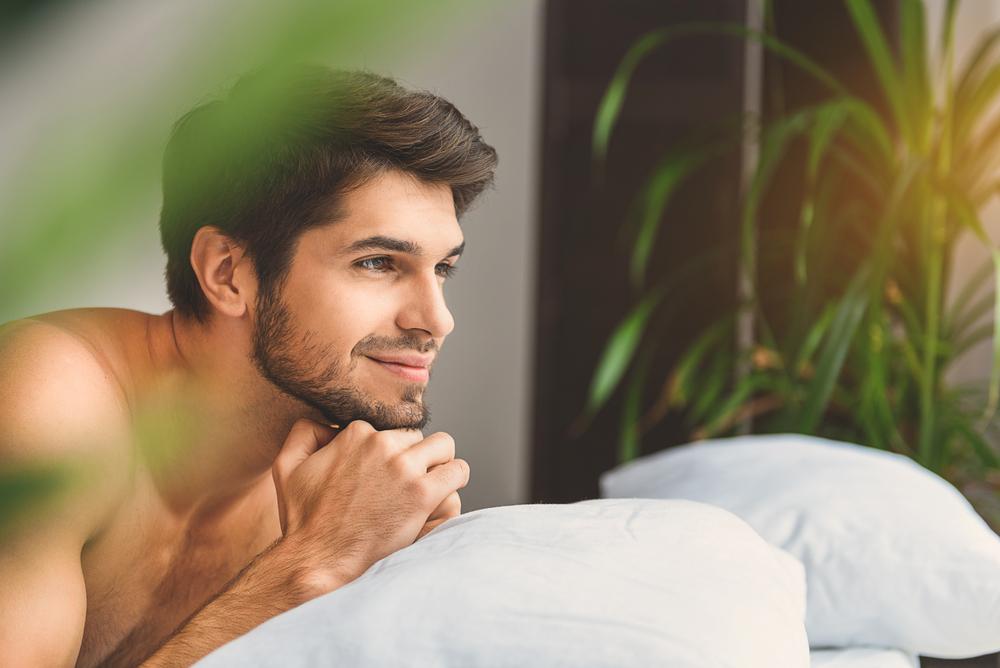 Drömmande kille som kopplar av i sovrummet