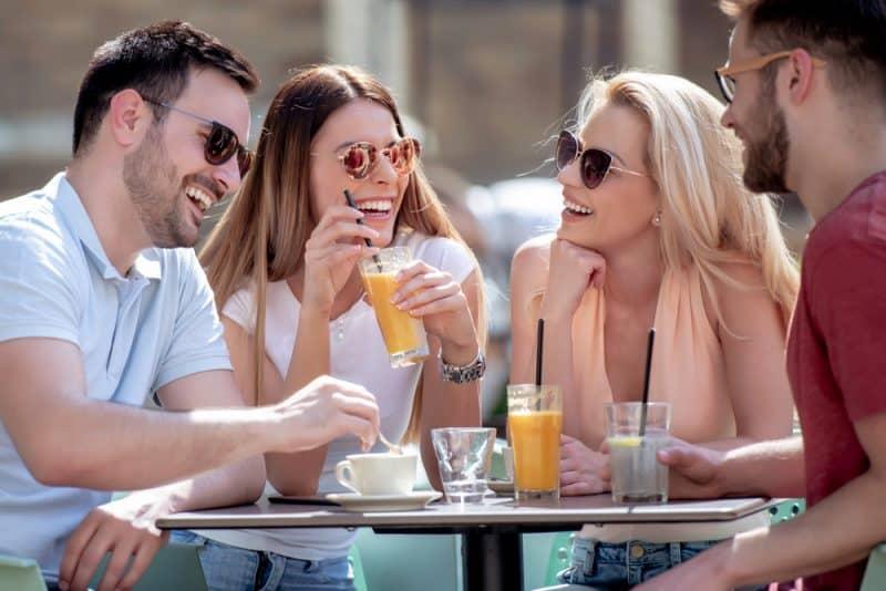 Grupp av fyra vänner som har kul på ett kafé tillsammans