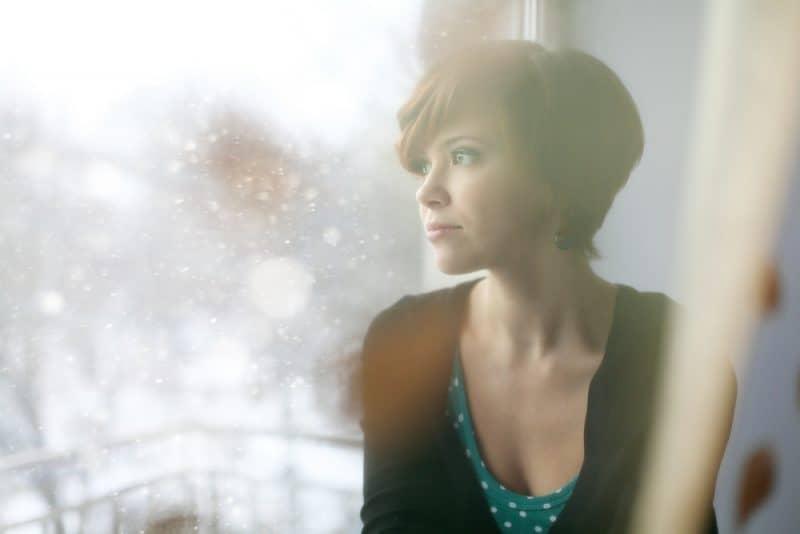 ledsen tjej i fönsterbrädan tittar ut genom fönstret