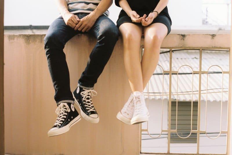 man och kvinnas ben när man sitter på staketet