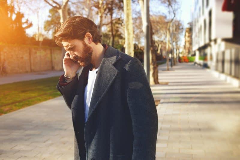 vuxen man pratar i mobiltelefon medan han står i staden