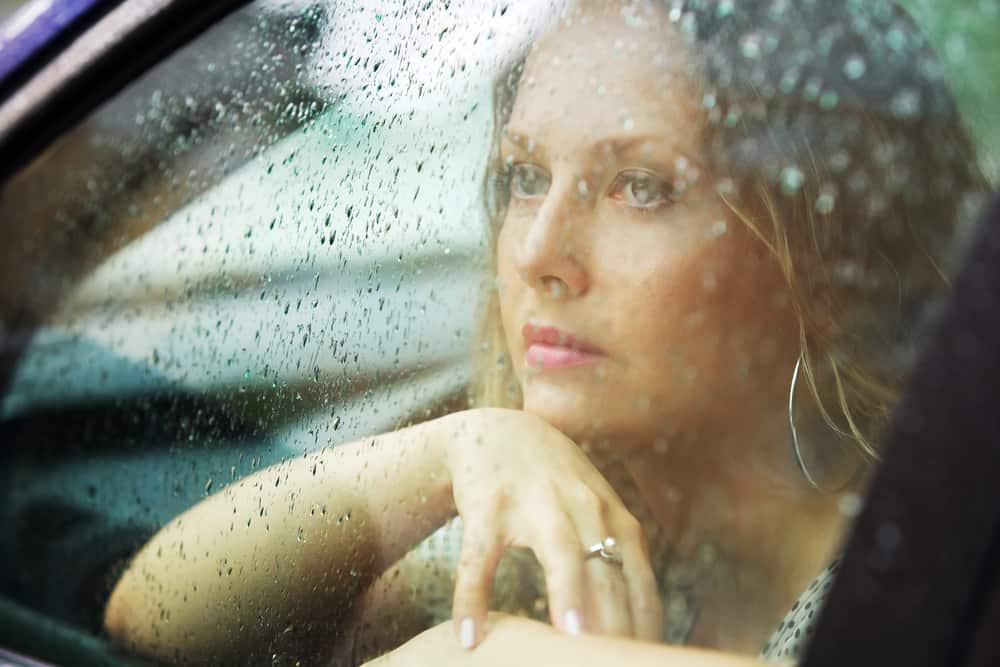 ledsen eftertänksam kvinna som tittar genom fönstret