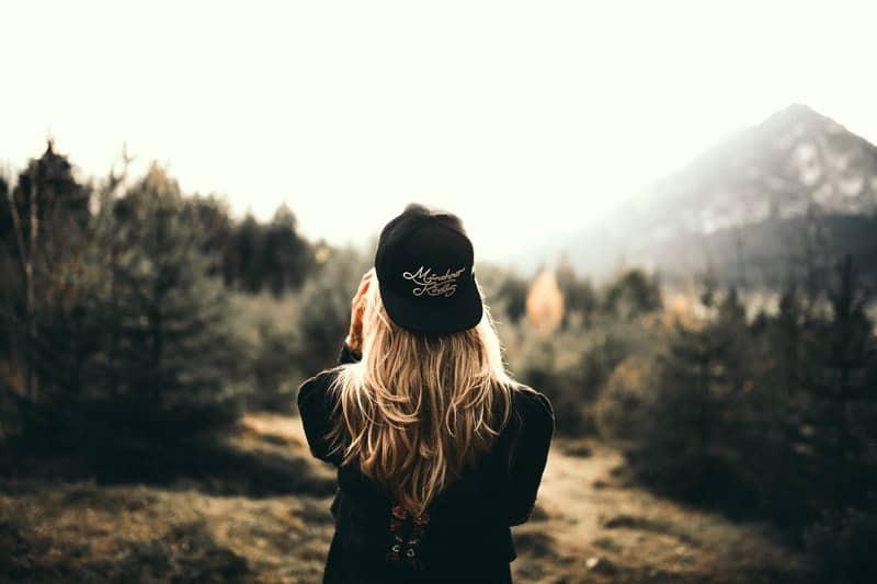 kvinna med locket ensam i skogen