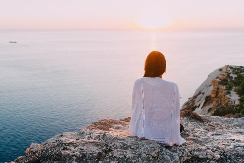 kvinna som sitter på kullen nära havet