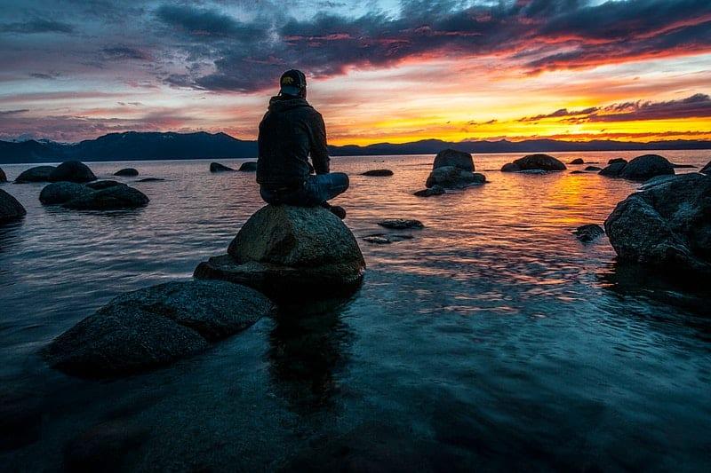 man sitter på klippan ovanför vattnet
