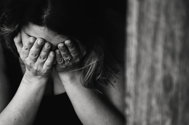 sorglig kvinna som täcker ansiktet med händerna