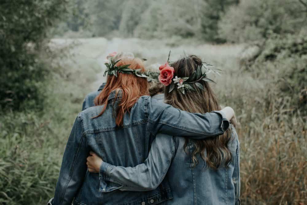två kvinnor som bär blåa jackor som kramar