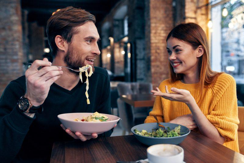 En man och en kvinna äter lunch på ett kafé