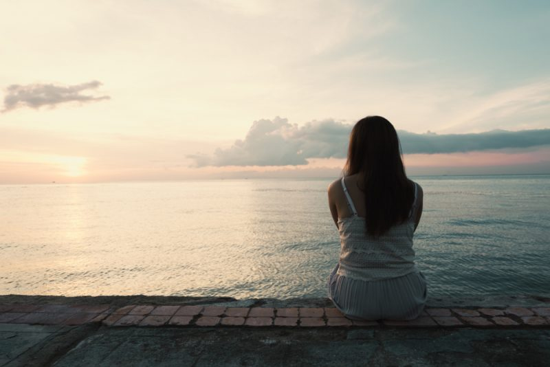 Kontur av den unga kvinnan som sitter ensam på baksidan utomhus