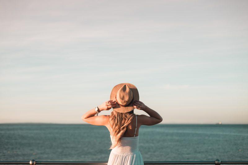 Kvinna som står vid räckeet som håller ögonen på havet