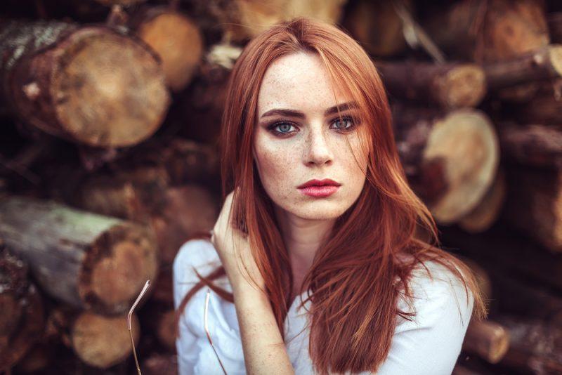 Porträtt av en ung öm rödhårig ung flicka
