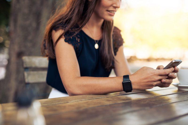 Skrivande textmeddelande för kvinna på smartphonen i ett kafé
