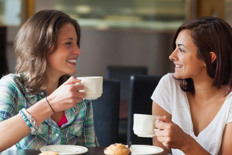 Två le studenter som har en kopp kaffe