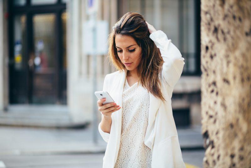 Ung affärskvinna som använder telefonen på gatan