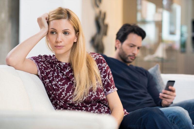 Ung kvinna som blir uttråkad medan mannen som använder telefonen i bakgrunden