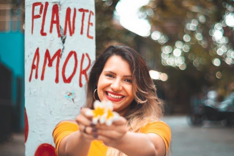 kvinna i gul skjorta som visar fotografering med gul blomma