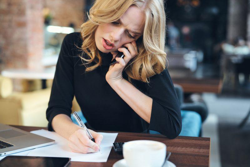 kvinnan är upptagen med att förhandla via telefon