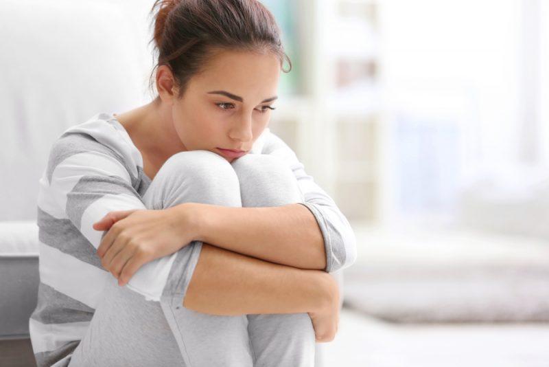 ledsen ung kvinna som sitter på golvet