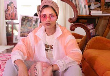 kvinna i rosa solglasögon som sitter i ett hus