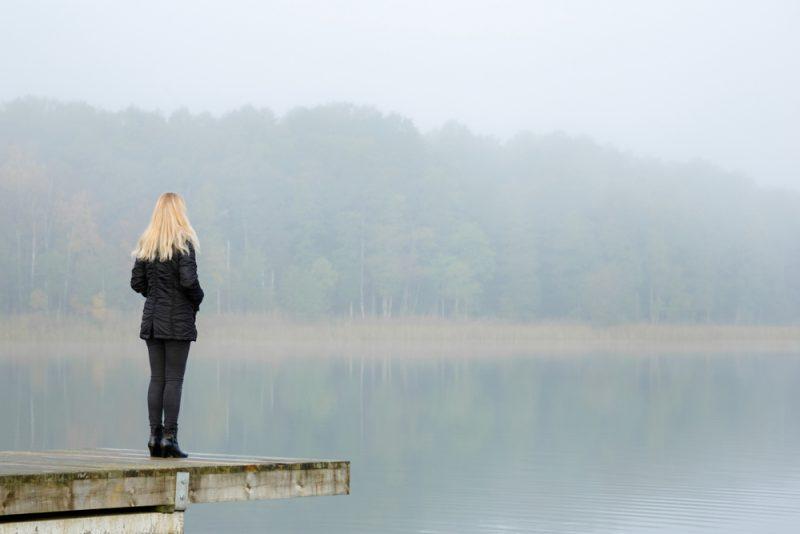blond kvinna som bär svart jacka som står ensam