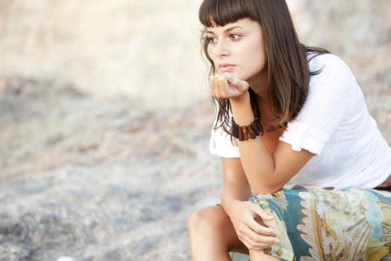 fundersam ung kvinna som sitter ensam