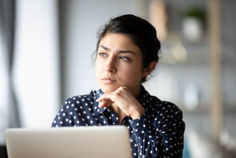 ledsen kvinna som sitter vid den bärbara datorn