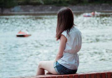 ensam kvinna som sitter nära vattnet