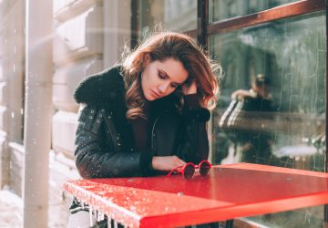 Olycklig tjej i gatukafé utomhus