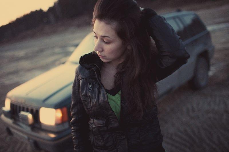 tankeväckande kvinna som står bredvid en bil