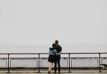 man som kramar kvinna nära havet