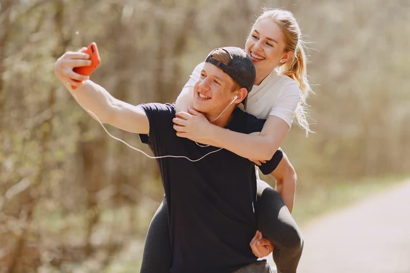 man bär kvinna och tar selfie