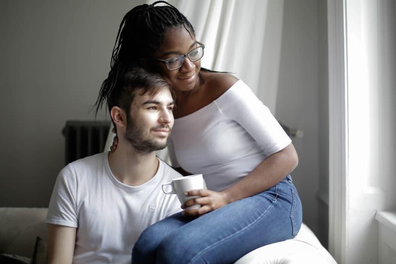 man och kvinna sitter och tittar genom fönstret