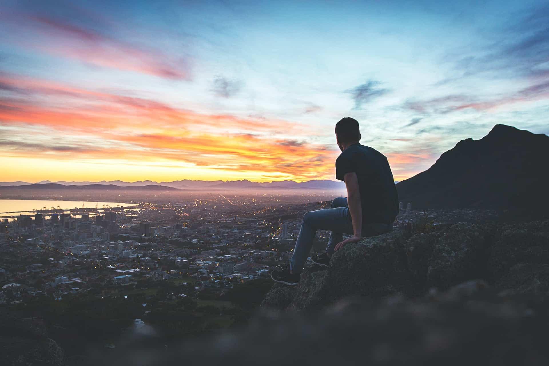 man sitter på kullen ovanför staden