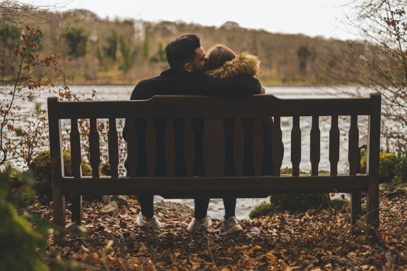 par som sitter nära sjön och kysser